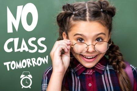 "portrait of schoolchild looking above glasses near blackboard, with ""no class tomorrow"" lettering"