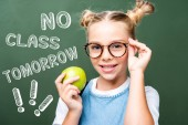 "schoolchild holding apple and touching glasses near blackboard, with ""no class tomorrow"" lettering"