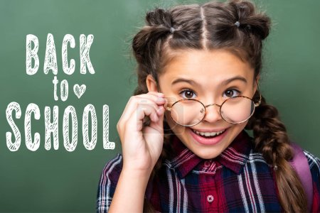 "portrait of schoolchild looking above glasses near blackboard, with ""back to school"" lettering"