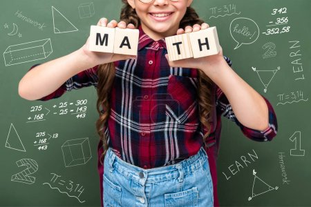 cropped image of schoolchild holding wooden cubes with word math near blackboard with mathematics symbols