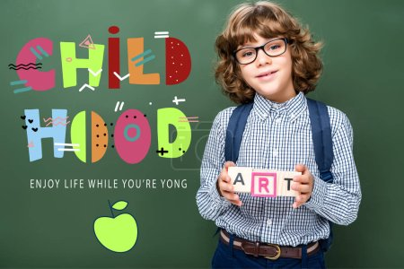 """schoolboy holding wooden cubes with word art near blackboard, with """"childhood"""" lettering"""