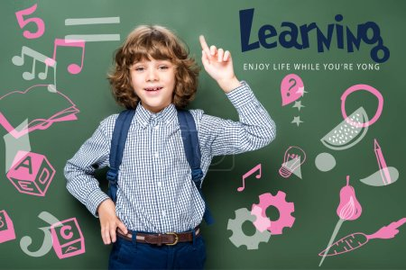 """Photo for Schoolboy showing idea gesture near blackboard, with icons and """"learning - enjoy life while youre yong"""" lettering - Royalty Free Image"""