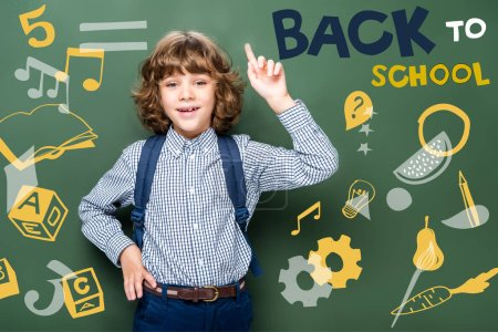 """schoolboy showing idea gesture near blackboard, with icons and """"back to school"""" lettering"""