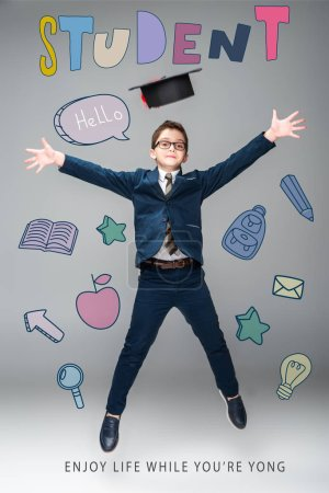 """Photo for Schoolboy in graduation cap jumping, isolated on grey with educational icons and """"student - enjoy life while youre yong"""" lettering - Royalty Free Image"""