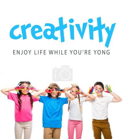 """Photo for Schoolchildren having fun and showing painted hands with smiley icons isolated on white, with """"creativity - enjoy life while youre yong"""" lettering - Royalty Free Image"""