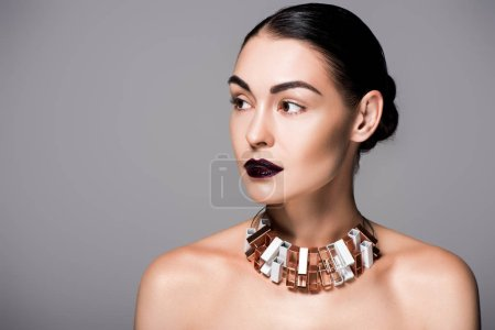 portrait of stylish nude girl posing wit black lips and trendy necklace, isolated on grey
