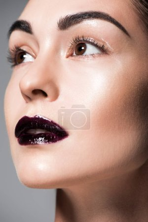 close up portrait of beautiful model with black lips, isolated on grey