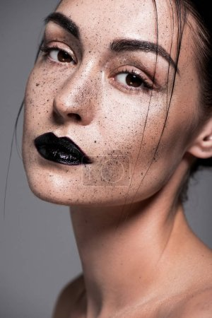 fashionable girl with black lips and freckles on face, isolated on grey