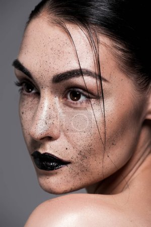 attractive model with black lips and freckles, isolated on grey