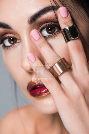 close up portrait of beautiful girl with golden rings on hand, isolated on grey