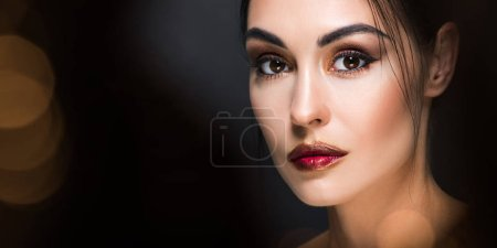 beautiful model with makeup posing on black with golden bokeh
