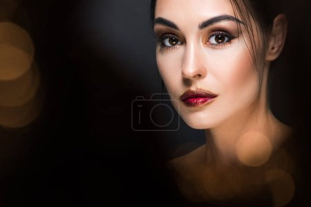 portrait of attractive woman with makeup posing on black with golden bokeh