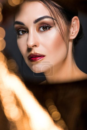 elegant fashionable model with makeup posing on black with golden bokeh