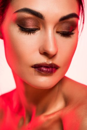 portrait of beautiful girl with closed eyes and makeup , red toned picture