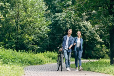 Photo for Happy young couple walking by park with vintage bicycle - Royalty Free Image