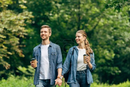 smiling young couple with paper cups of coffee walking by green park together