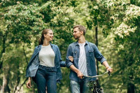 Photo for Happy young couple in denim shirts with bicycle walking by park - Royalty Free Image