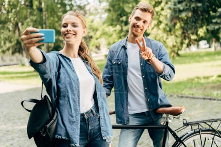 Photo for Beautiful young couple with vintage bicycle taking selfie together at park - Royalty Free Image