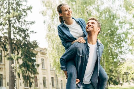 Foto de Mujer joven feliz piggybacking a su novio en el Parque - Imagen libre de derechos