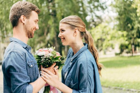 happy young couple holding flower bouquet at park and looking at each other