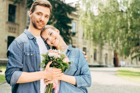 happy young couple holding flower bouquet at park and looking at camera