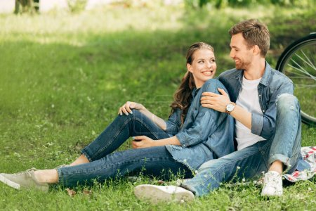 Photo for Happy young couple sitting on grass at park together - Royalty Free Image