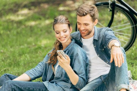 Photo for Happy young couple using smartphone together at park - Royalty Free Image
