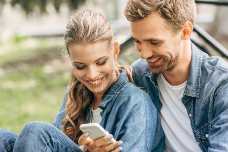 Photo pour Beau jeune couple en utilisant smartphone ensemble au parc - image libre de droit