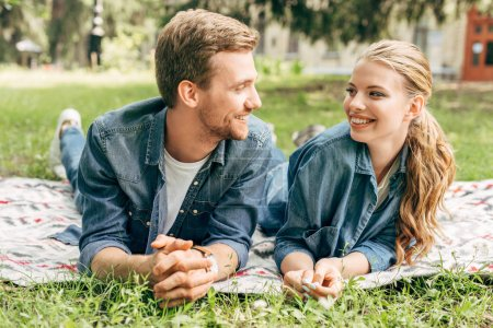 Photo for Happy young couple lying on grass at park and looking at each other - Royalty Free Image