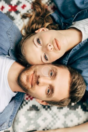 top view of beautiful young couple lying on patterned cloth and looking at camera