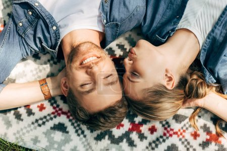 Photo for Top view of happy young couple with closed eyes lying on patterned cloth - Royalty Free Image