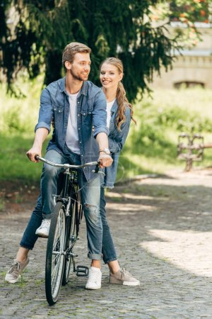Photo for Beautiful young couple riding vintage bicycle together at park - Royalty Free Image