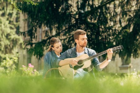 Photo for Attractive young man playing guitar for his girlfriend during picnic at park - Royalty Free Image