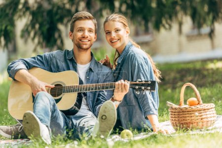 happy young man playing guitar for his smiling girlfriend during picnic at park and looking at camera