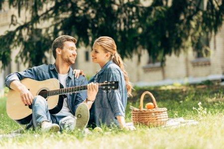 attraktiver junger Mann spielt Gitarre für seine lächelnde Freundin beim Picknick im Park