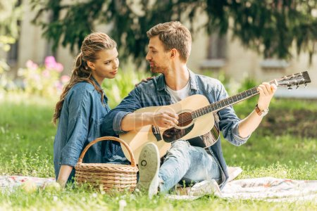 Photo for Handsome young man playing guitar for his smiling girlfriend during picnic at park - Royalty Free Image