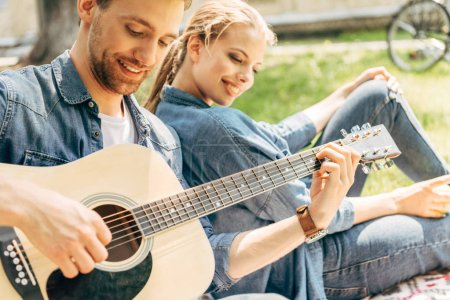 handsome young man playing guitar for his smiling girlfriend while relaxing at park