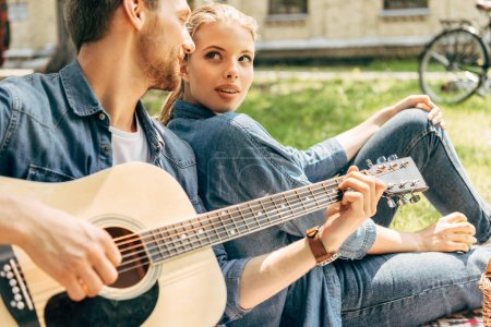 Photo for Handsome young man playing guitar for his girlfriend while relaxing at park - Royalty Free Image