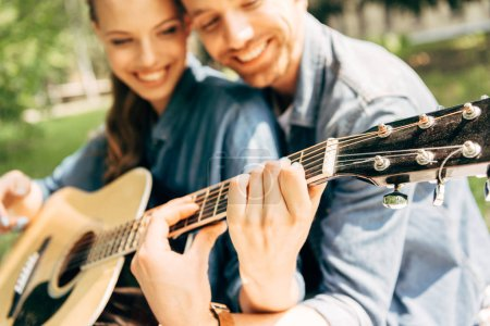 close-up shot of young happy woman with boyfriend playing guitar together at park