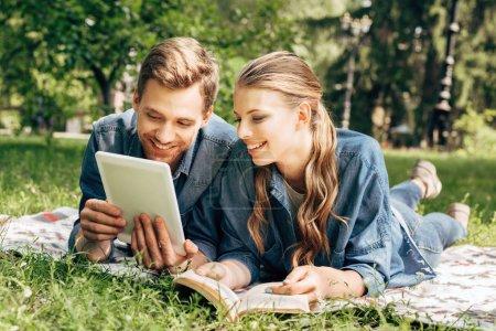 happy young couple lying on grass at park and using tablet