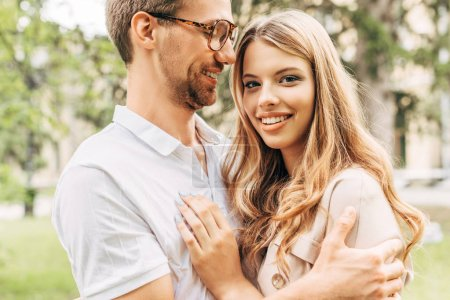 bottom view of happy young couple embracing at park