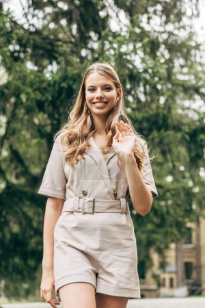 smiling young woman in stylish overall looking at camera and waving with hand
