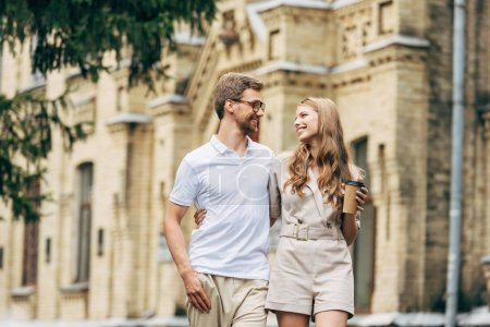 Photo for Happy young couple taking walk together and looking at each other - Royalty Free Image