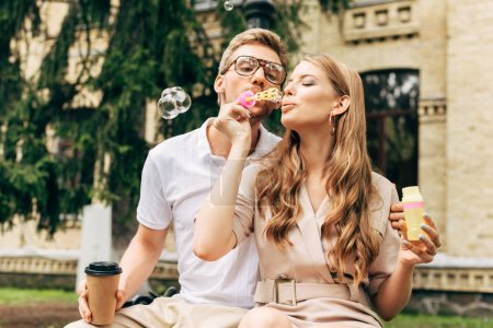stylish young couple blowing soap bubbles together