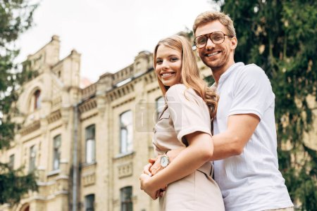 bottom view of beautiful young couple embracing near old building