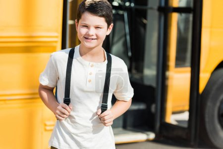 smiling little pupil with backpack standing in front of school bus