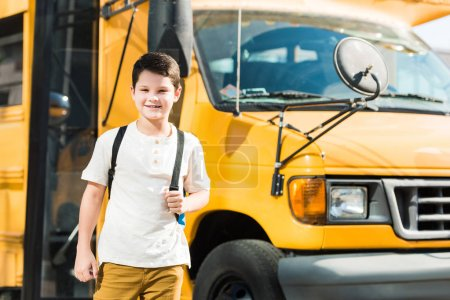 happy little pupil with backpack standing in front of school bus
