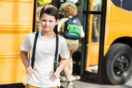serious little schoolboy looking at camera in front of school bus