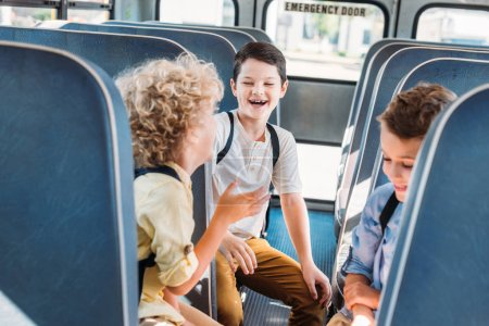 group of adorable schoolboys having fun together while riding on school bus