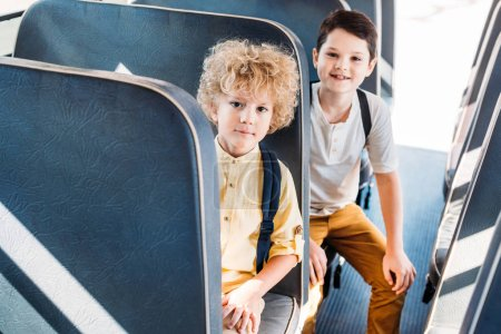 cute little schoolboys sitting in school bus and looking at camera